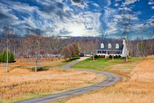 A nice white farmhouse down a long driveway across winter lawn
