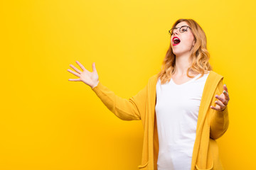 young pretty blonde woman performing opera or singing at a concert or show, feeling romantic, artistic and passionate against yellow wall