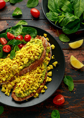 Scrambled Tofu crispy Toast with guacamole and spinach, tomato salad. Vegan vegetarian, plant based food