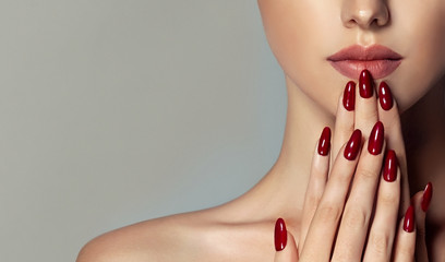 Beautiful girl   . Model woman showing  red  shellac manicure on nails   . Cosmetics ,beauty and...