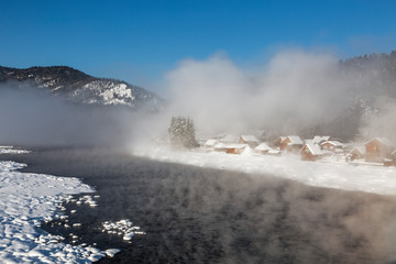View of the winter Altai with the Biya river, fog over the river, Artybash village and mountains on the horizon. Altai Republic, Russia