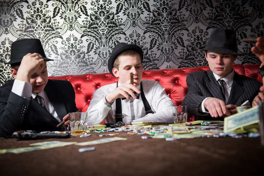 Mafia party in restaurant 1920 style. Gangsters sitting at the table, party mafia. man  share the money won.