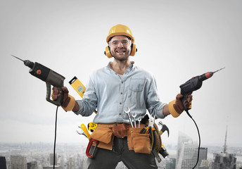 Construction worker with a hammer and drill at work