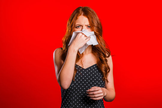 Young girl sneezes into tissue. Isolated on red woman is sick, has stuffed or runny nose and fever. Coronavirus, epidemic 2020, illness concept.