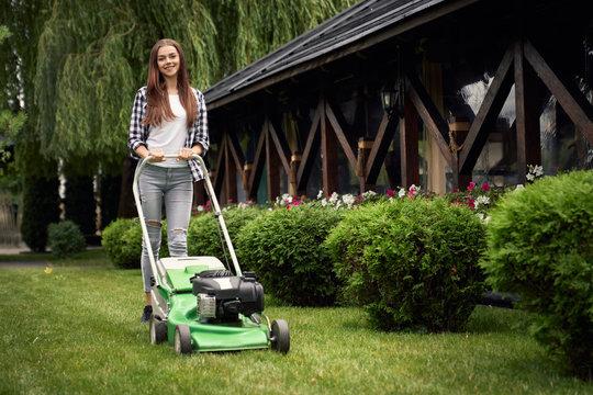 Female gardener using lawn mower.