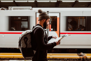 Foto op Canvas Wenen .Attractive young man with beard waiting at the train station in Vienna. Thinking about his trip, with the map in his hand and a backpack. Travel photography.