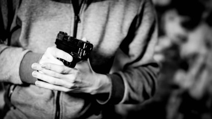 """Man holding pistol at the """"low ready"""" position in black and white"""