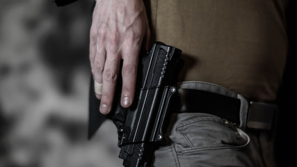 Man reaching for a pistol on his belt. Open carry and second amendment concept.