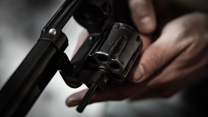 Man inspecting the chamber of a .38 special revolver. Close up of firearm mechanism.