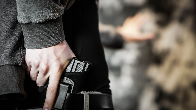 Man holding out hand while drawing a concealed pistol. Personal protection concept