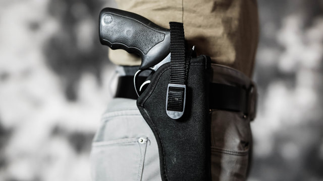 Man openly carrying a revolver on his belt. Open carry and second amendment concept.