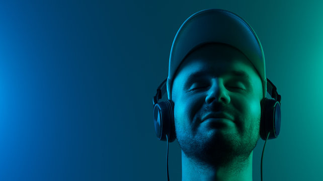 Satisfied young man listening to music on headphones. His eyes are closed. Copy space