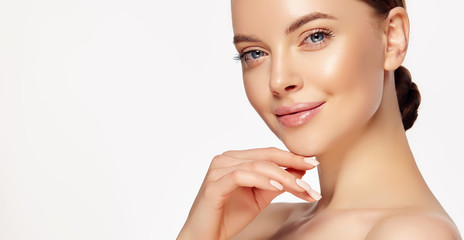Beautiful young woman with clean fresh skin touching her face . Girl facial  treatment   . Cosmetology , beauty  and spa . Female  model, care concept