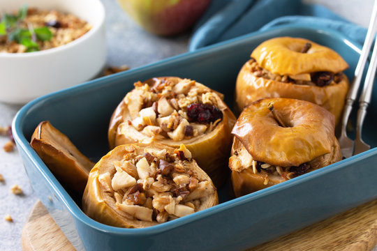 Diet menu. Healthy dessert. Baked apples with walnuts, honey and granola on slate, stone or concrete background.