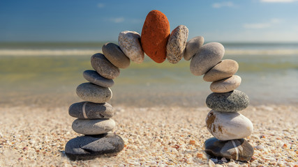 Poster Stones in Sand Stone arch with red stone at top in the morning on a beach. Wellness and nature concept.