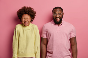 Cheerful overjoyed nice girlfriend and boyfriend laugh toothily, express positive emotions, enjoy joke, chuckle at camera, stand next to each other against pink pastel background listen humorous story