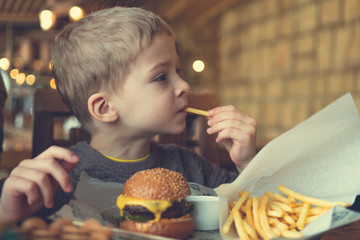 child eats a mini Burger and fries. children's menu in the cafe