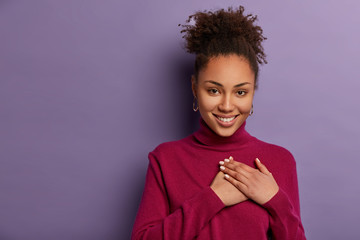 Smiling lovely curly girl impressed by touching moment, presses palms to chest, feels thankful for help, has curly combed hair, wears casual burgundy jumper, models over purple wall, blank space
