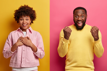 Portrait of pleased thankful woman keeps hands on chest, expresses gratitude and smile pleasantly, overjoyed bearded man clenches fists with triumph, express positive emotions. Afro American couple