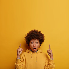 Wow, look there! Impressed shocked woman with Afro hair points fore fingers above, shows blank...