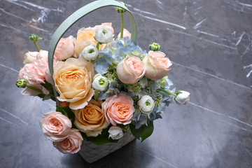 Tuinposter Lelie A bouquet of fresh flowers of roses, anemones and gartensia in a basket on a stone background.