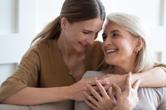Adult daughter hug senior mother showing love at home