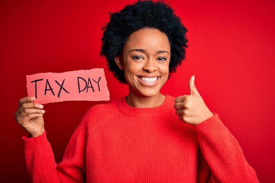 Young African American afro woman with curly hair holding paper with tax day message happy with big smile doing ok sign, thumb up with fingers, excellent sign