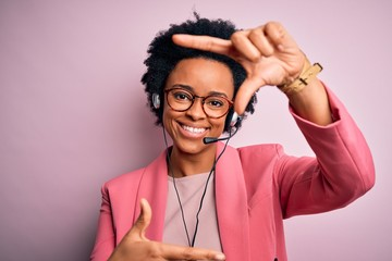 Young African American call center operator woman with curly hair using headset smiling making frame with hands and fingers with happy face. Creativity and photography concept.