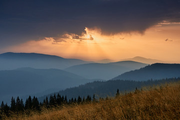 Majestic landscape of mountains at sunrise. View of the misty tops and layer hills of the mountains in the distance. Dramatic sky and rays of sunlight at morning. Concept of nature background.