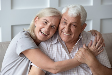 Headshot portrait of happy elderly couple embracing Wall mural