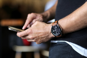 Man checking his smartphone while wearing a stylish wrist hand watch. Technology and class concept. Modern mobile phone. Social media and business person