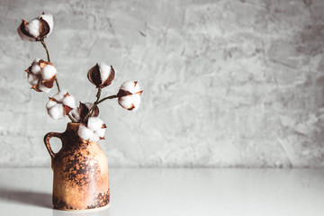 branches of cotton in a brown wicker vase on a background of a gray-blue wall