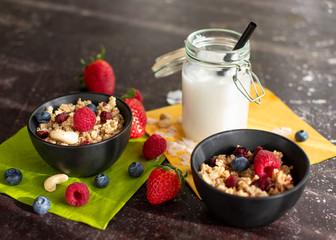 Müsli mit frischen Beeren in schwarzen Schälchen. Dazu Kokosmilch im Einmachglas mit Strohhalm