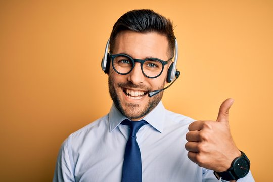 Young business operator man wearing customer service headset from call center doing happy thumbs up gesture with hand. Approving expression looking at the camera showing success.