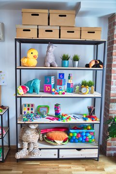 Shelving with lots of  colorful organized toys at kindergarten