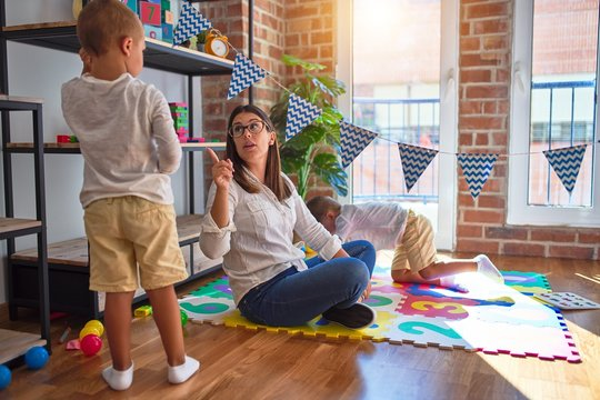 Beautiful teacher angry poiting with finger to toddler around lots of toys at kindergarten