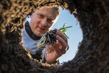 Foto vom Einpflanzen einer Blumenzwiebel aus besonderer Perspektive Fototapete