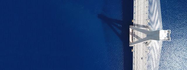 Aerial drone ultra wide photo of suspension cable bridge over deep blue sea