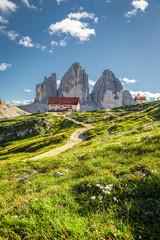 Wall Mural - Mountain shelter Dreizinnen hut and green hills in Dolomites, Europe