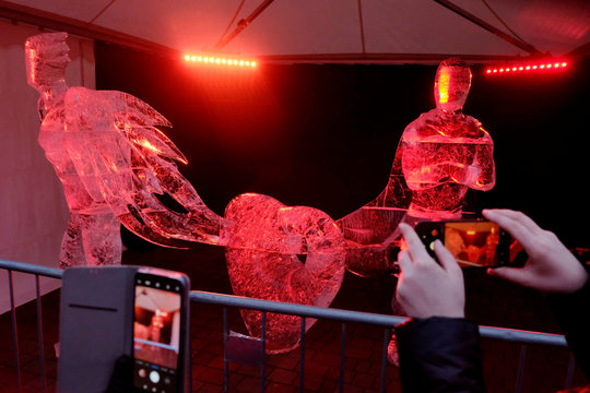 A woman takes a picture of an ice sculpture called 'Superheroes Friends' during the International Ice Sculpture Festival in Jelgava