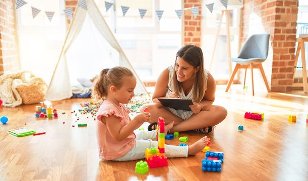 Beautiful psycologist and blond toddler girl doing therapy building tower using plastic blocks at kindergarten