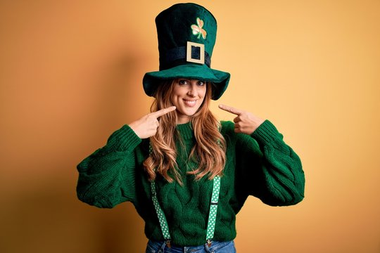 Beautiful brunette woman wearing green hat with clover celebrating saint patricks day smiling cheerful showing and pointing with fingers teeth and mouth. Dental health concept.