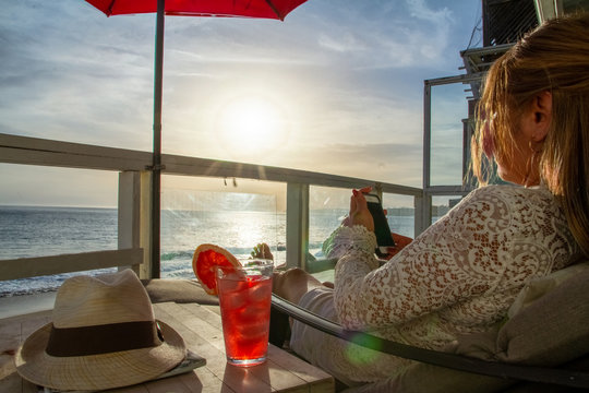 Attractive woman texting on phone with a refreshing drink at a deck with a ocean view