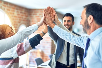 Group of business workers standing with hands together highing five at the office Wall mural