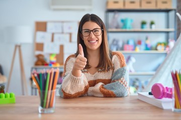 Young beautiful teacher woman wearing sweater and glasses sitting on desk at kindergarten doing happy thumbs up gesture with hand. Approving expression looking at the camera showing success.