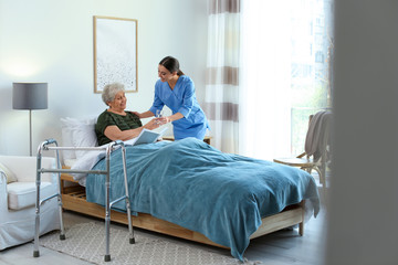 Care worker giving water to elderly woman in geriatric hospice