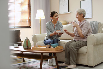 Young woman serving dinner for elderly woman in living room. Senior people care