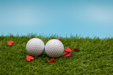Golf ball and red heart with tee are on green grass with blue sky background for golfer on Valentine's Day or Wedding Invitation