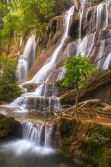 Vertical Landscape View of Scenic Kuang Si Falls, a beautiful cascading Waterfall in a Lush Forest Setting near Luang Prabang, Laos Southeast Asia