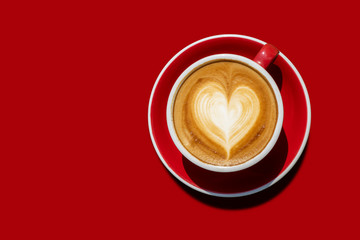 Photo sur Aluminium Cafe Top view Hot cappuccino coffee And with a cream like the heart in a red cup placed on red tone ground. isolated with clipping path. love and coffee concept for backdrop